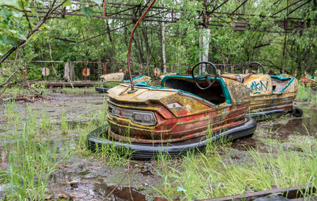 abandoned: rusty cars in abandoned playground of Pripyat park, Chernobyl