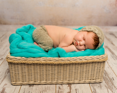 funny asleep newborn baby in wicker cot with knitted hat and pants