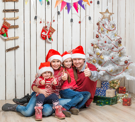 big family in red santa hats near the faux christmas tree in studio photo