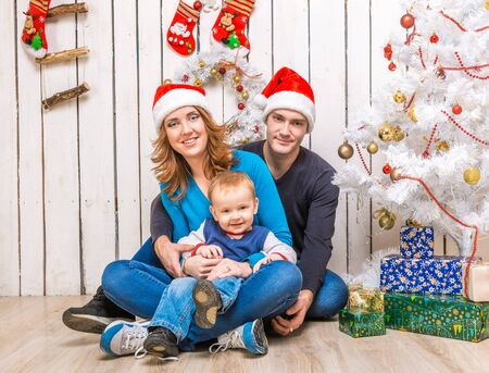 young family in red hats with little son sitteng near the christmas tree