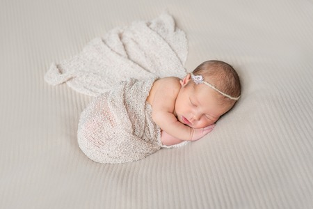 swaddled: lovely smiling sleeping infant wrapped in gray warm diaper