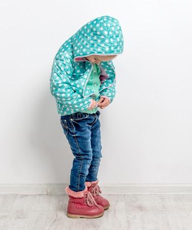 little girl fastening her blue jacket Фото со стока