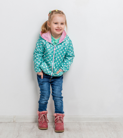 trendy little girl in jeans, jacket and boots