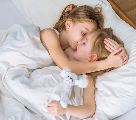 naughty child: two little sisters hugging in bed Stock Photo