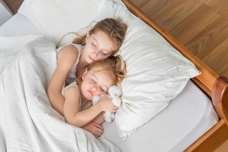 bedsheets: two little sisters hugging in bed Stock Photo