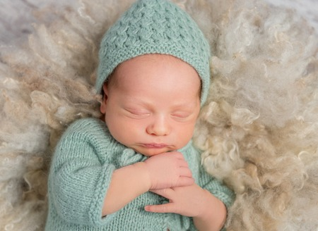 overalls: lovely newborn in hat and overalls sleeping