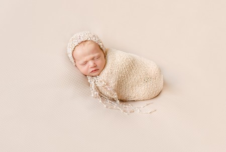 lovely wrapped baby in hat sleeping on a beige blanket