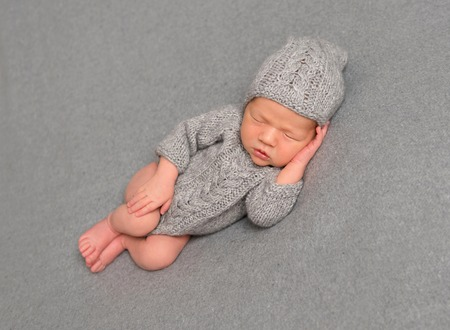 Infant asleep in a knitted outfit Stock Photo