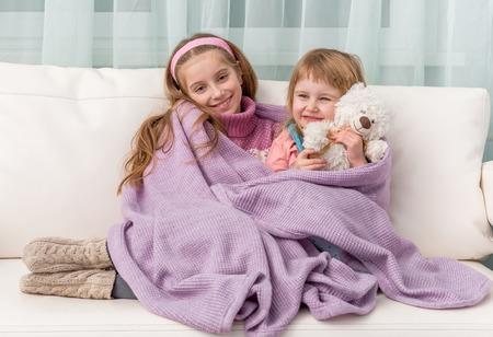 twee mooie kleine meisjes op de sofa