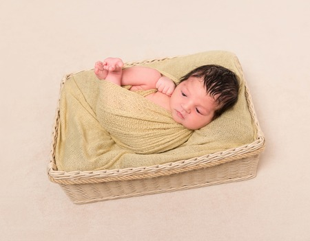enveloped: Wrapped black-haired baby basket, topview Stock Photo