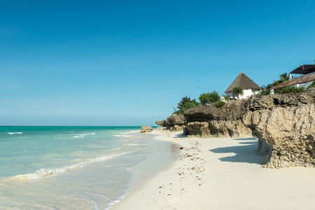 beautiful seascape with thatched houses on Zanzibar beach