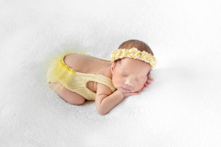 Baby dressed in a yellow outfit sleeping Stock Photo