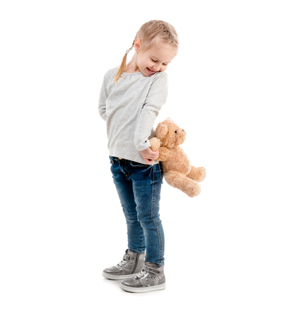 Girl peaking on a teddy, isolated Stock Photo