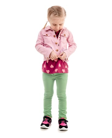 Child trying to zip her pink coat, isolated