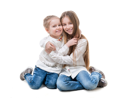 Siblings hugging, isolated on white background