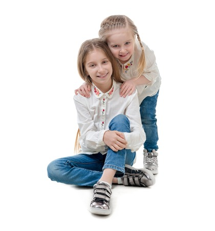 Two sisters holding each other, isolated