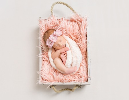 Baby girl on soft pink blanket, topview