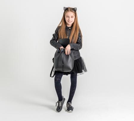 Modieus tienermeisje in een zwarte jas Stockfoto