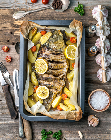 Appetizing baked fish with lemons, topview Фото со стока