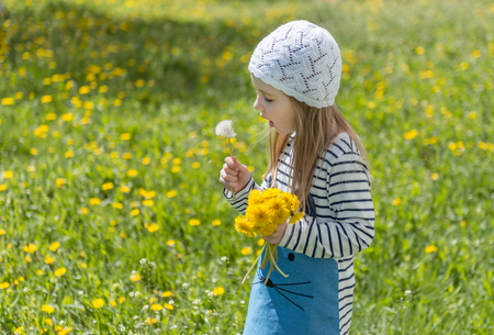 Little girl playing with yellow flowers outside