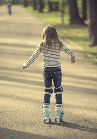 girl roller blading in park, back to camera Stock Photo