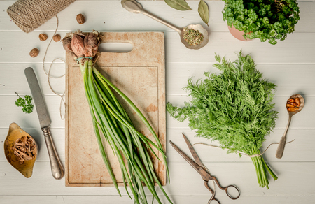 Green onion, dill on the cutting board, topshot