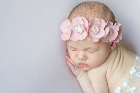 girl with pink flowers on her head napping