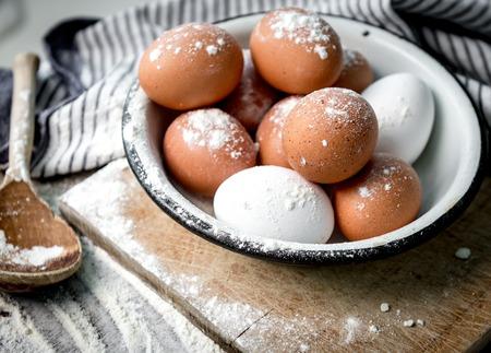 eggs in tin bowl, brown spoon, blue napkin