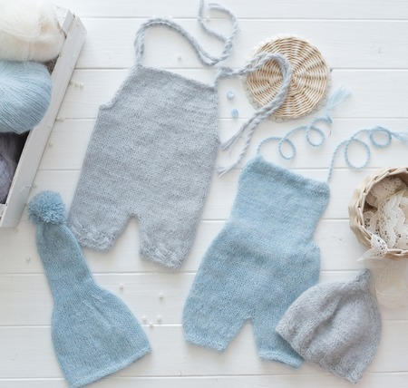 Simple knitted handmade clothes for infant boys, pants and hats, blue and pastel gray, topview
