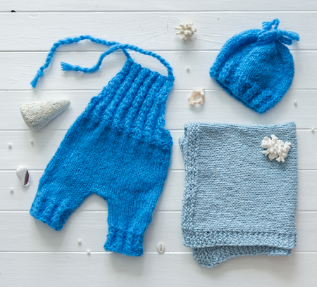 Cute blue pants and hat, blanket for babies, handmade knitted, designed as sea costume, topview Фото со стока