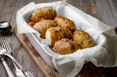 Baked sliced potatoes sitting in dish, rustic dishware
