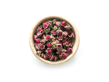 Exotic tea, roses buds in rustic bowl, topview