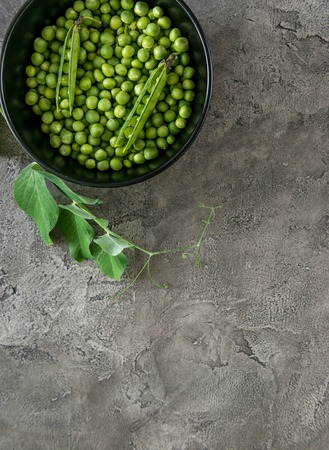 Black bowl with green peas, topview, copyspace