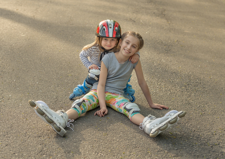 blading: Two sisters roller skating together, wearing protection