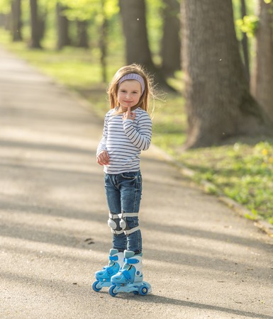 girl with helmet and skates in alley Stock Photo