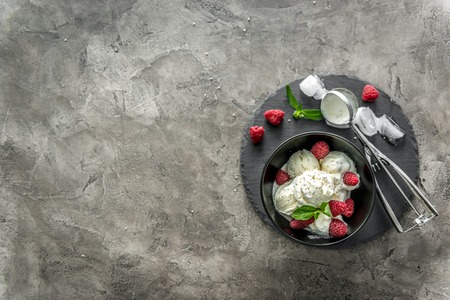 ice cream with raspberries served in black piala