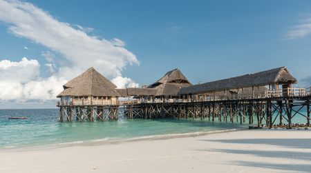 beautiful wooden pier with thatched huts in ocean
