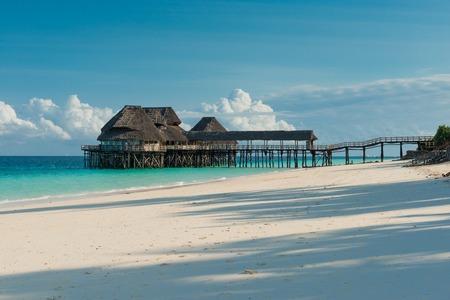 Belle jetée en bois avec cabanes de chaume en océan Banque d'images - 83148088