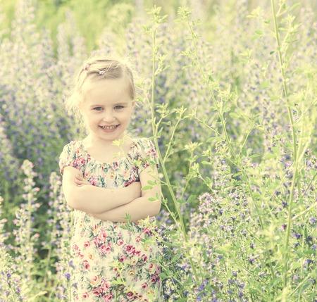 Petite fille avec les bras croisés, champ de printemps Banque d'images - 83209348