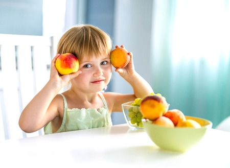 cute little girl with peaches in hands at the table