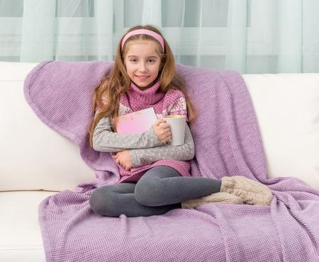 책이있는 소파에 어린 소녀
