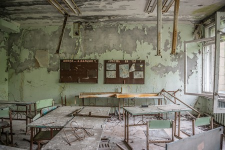 abandoned class room with furniture and debris in Pripyat