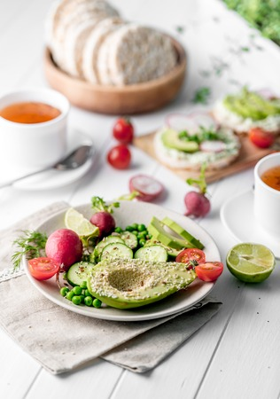 Flatbread with avocado and raddish, cup of tea