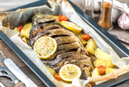 Delicious baked fish with lemons, spices Banco de Imagens - 85210147