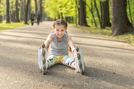 girl rollerblading sitting on asphalt, stretching Фото со стока