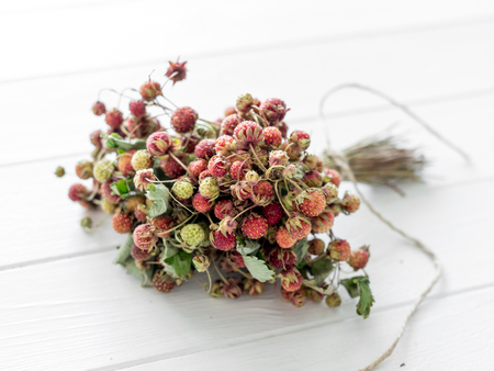 A bunch of strawberry dried for tea on a wooden background
