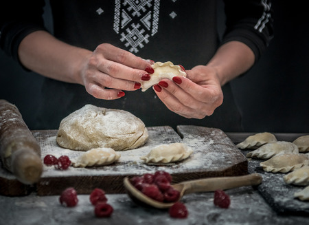 Woman makes varenyky with raspberry