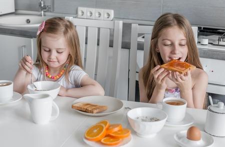 姉妹のブランチ、オート麦、蜂蜜とトーストを食べる