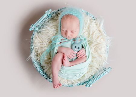 sweet newborn wrapped in a nappy sleeping on a round rug