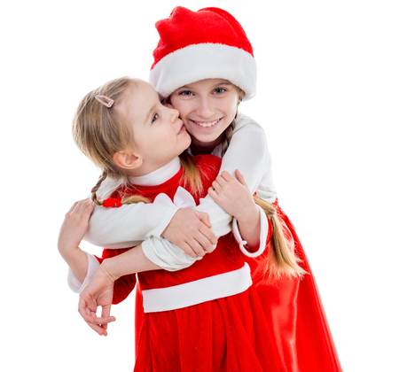 two happy little girls in santa suits embracing Stock Photo